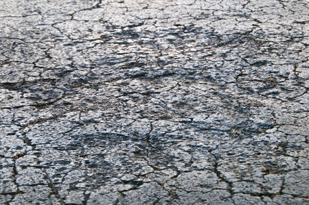 Low angle close up view of cracked and damaged roadway tar asphalt.