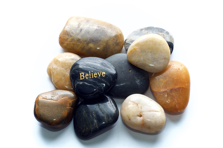 A gray polished river stone with the word believe in gold on a pile of many polished rocks. Over white, not isolated.