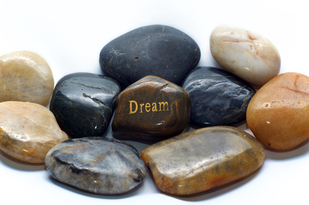 A brown polished river stone with the word dream on it surrounded by many other rocks. Over white, not isolated.