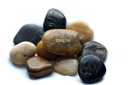 A brown polished river stone with the word imagine on a pile of many polished rocks. Over white, not isolated.