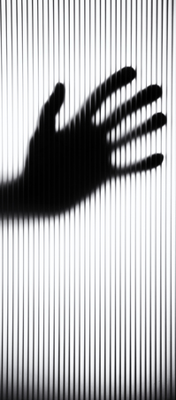 A back lit hand is pressed up against a frosted rippled pane of glass in doorway. texture of glass makes hand look like it is dripping and distorted.