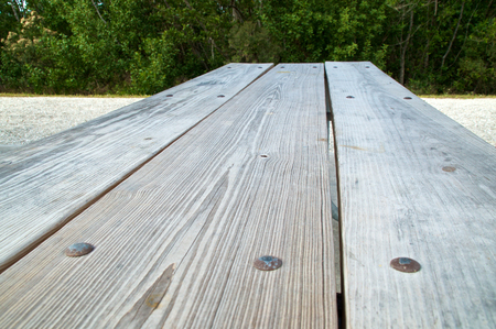 Low angle view of old weathered wooden picnic table top extending into the distance. Stock Photo