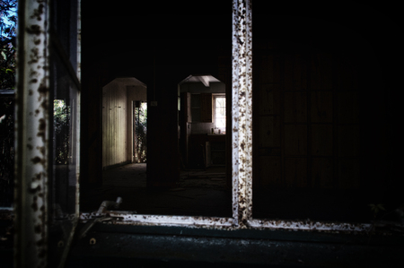 Looking into a dark abandoned home from window showing doorway and kitchen. Noise at 100%