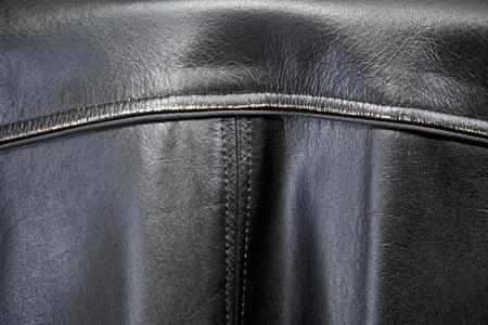 Detail of old leather biker jacket focusing on back seams. 免版税图像