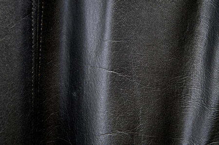Detail of old black cow leather biker jacket. Фото со стока