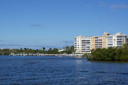 Scenic view of Bonita Springs Florida, looking across canal towards large building and boat docks. Imagens