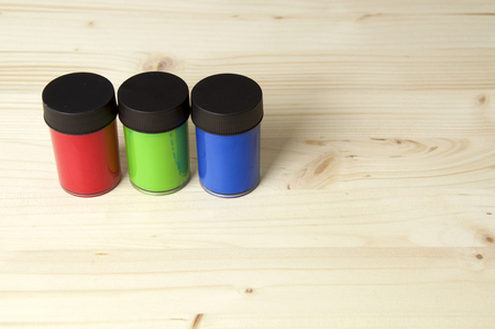 RGB, Red, green, and blue paint lined up on wooden surface with copy space.