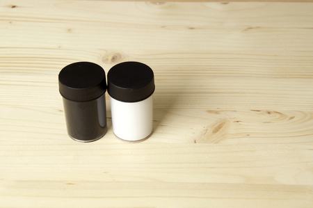 Black and white paint in plastic containers on wooden surface with copy space..
