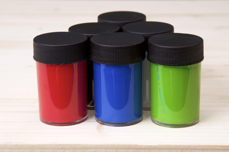 Six plastic containers of watercolor acrylic paint showing red, green, and blue on drawing board.