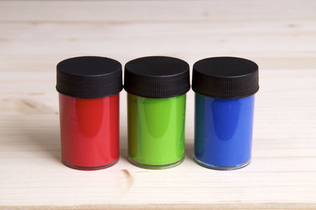 Three plastic containers of watercolor acrylic paint in red, green, and blue on drawing board.