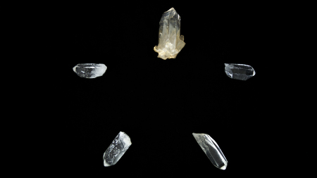 five clear quartz crystal points on black background, forming a pentagram, pentacle, or star.