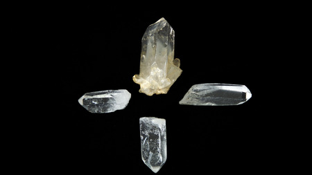 Four large clear quartz crystal points on black background, one pointing in each direction forming a cross. Фото со стока
