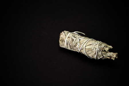 A bundle of dried white sage used for smudging on black background used by native americans for cleansing and shamanic ceremonies. Stock Photo