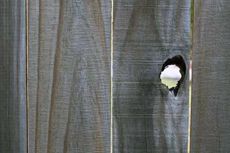 Close up of old wooden fence with open knothole creating a large peephole.