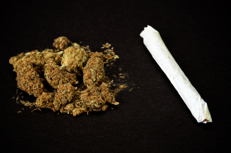 pile of buds of cannabis and marijuana cigarette on black background. Used as a recreational drug and also alternative medicine.