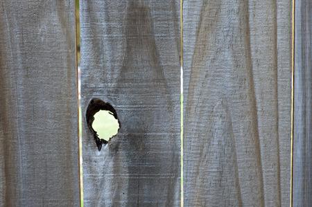 Close up of old wood fence with open knothole creating a large peephole. 版權商用圖片