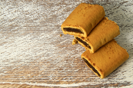 stack of three fig bar cookies on old wooden background or counter.