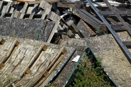 A heap of wooden pallets or skids and sheets of particle boards in a pile outdoors in sunlight. Stok Fotoğraf