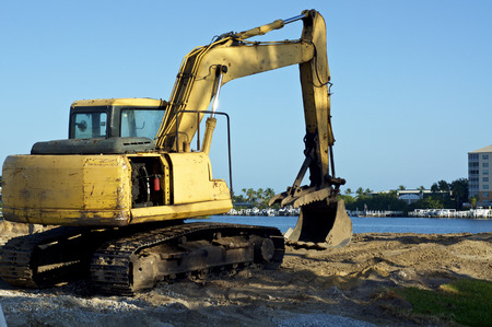 A yellow front end bucket loader excavator sits on land at the water's edge at bay in Bonita Springs Florida on a sunny morning.