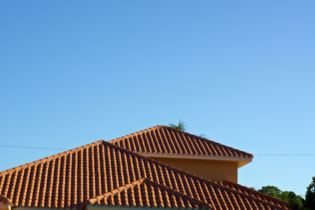 View of three orange terra cotta clay roof tops against a clear blue sky in bonita springs florida with deep shadows from morning light.