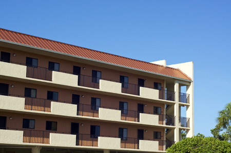 View of three story generic housing building in Southwest Florida on a sunny morning with clear blue sky.