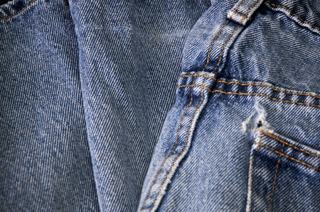 Close up of pair of worn faded blue jeans showing stitching and hole in pocket.