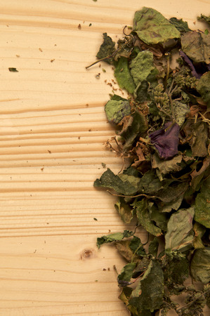 A large pile of dried Patchouli, Pogostemon cablin, leaves and flowers used for aromatherapy and incense on wood with copy space. Member of the mint deadnettle family. 스톡 콘텐츠