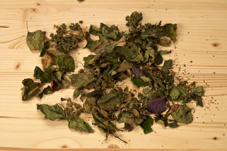 A large pile of dried Patchouli, Pogostemon cablin, leaves and flowers used for aromatherapy and incense on plain wood surface. Member of the mint deadnettle family. Banco de Imagens - 122264915