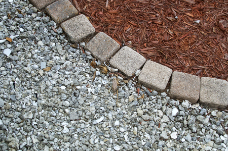 Looking down at square bricks form curve that separates mulch from gravel or small stones in backyard garden area with copy space. Banco de Imagens