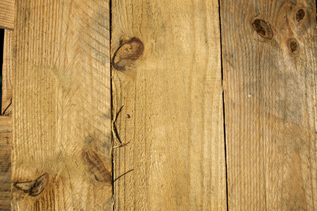 Three rough knotty planks of pine wood lined up side by side in the sunshine.