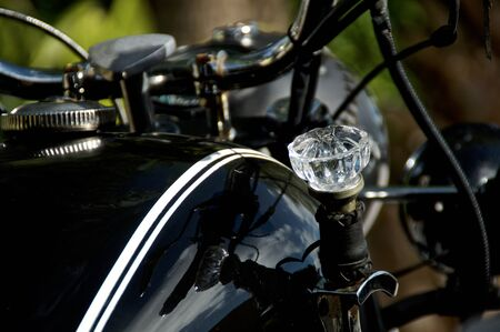 Close up of crystal diamond shaped doorknob used as shifter on old black vintage motorcycle.
