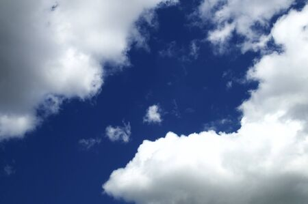 Blue sky cutting through at an angle dividing bright clouds.