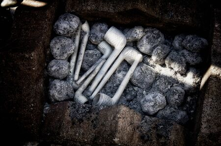 Stylized image of and assortment of clay pipes being cleaned on bed of charcoal in brick  fire pit,