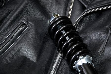 Close up of brand new clean black and silver motorcycle shock absorber is laying across an old worn leather biker jacket with zippers. Banco de Imagens