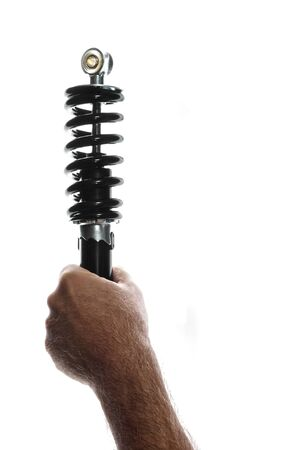 A man is holding up new motorcycle shock, over white backlit, with copy space.  this shock is also used on ATVs.