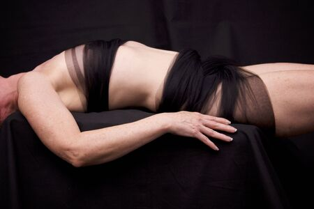 Side view of anonymous pale freckled woman laying down against black background wearing mesh fabric.