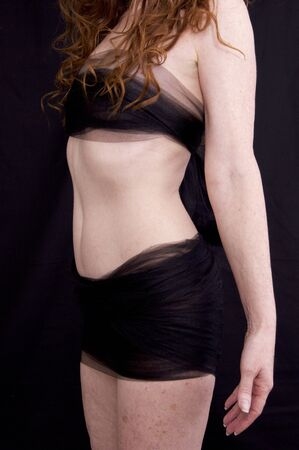 Three quarter view of anonymous pale freckled red haired woman torso with arms at side against black background wrapped in mesh fabric.