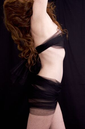 Side view of anonymous pale freckled red haired woman torso with arms raised against black background wrapped in mesh fabric.