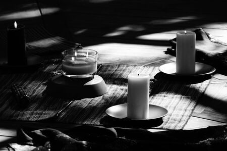 Black and white candle lit image with deep shadows, showing center of pagan mayan ceremonial setting, with corn cobs and candles.
