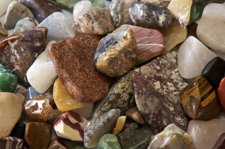 Numerous and various sized colorful and vibrant polished stones fill the image.