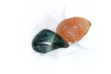 Two large stones on white background, quartz and polished jade.