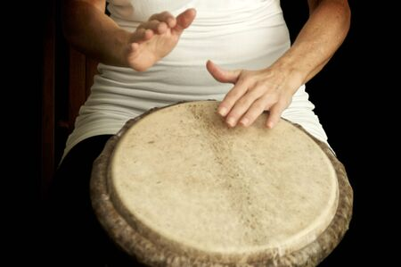 Woman's hands in motion as she drums on top of goat skin covered drum against dark background. Stok Fotoğraf