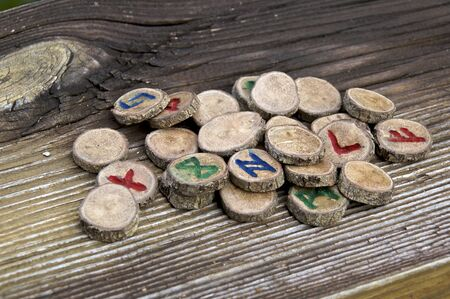 Collection of carved oak branch runes, known as the germanic futhark, on weathered wooden plank, used in magic and divination Banco de Imagens