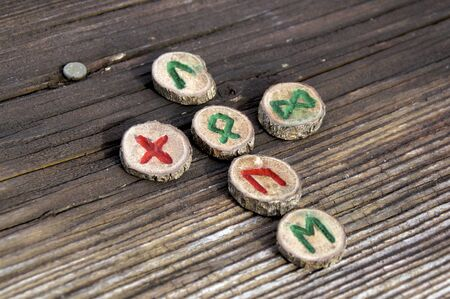 The words love and god spelt out in runes,  known as the germanic futhark, on weathered wooden plank, used in magic and divination.