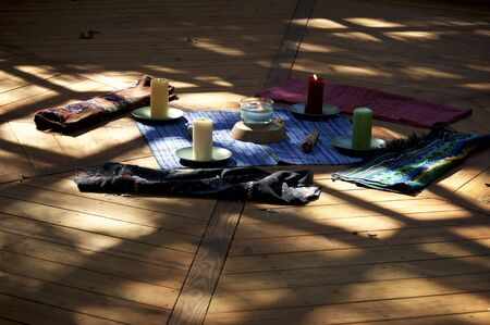 Center of pagan mayan ceremonial prayer space, with corn cobs, woven fabric and candles for the 5 elements or directions.