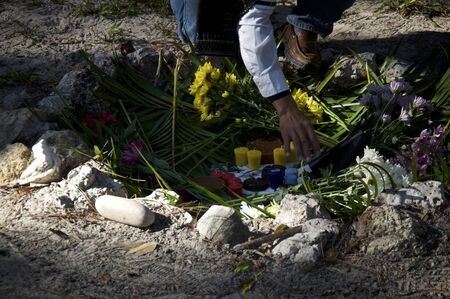 A mayan priest is preparing ceremonial offerings of chocolate, flowers, colored candles and more in a stone fire pit.