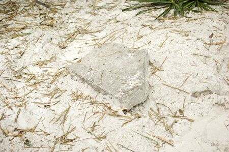 A broken cement slab sits on fine soft white dirt known as sugar sand in southwest florida.