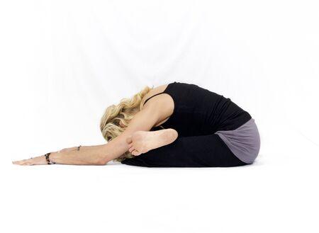 Blonde woman on white background doing seated yoga forward fold pose.