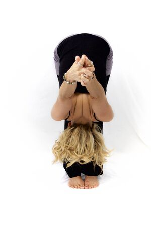Blonde woman standing on white background in yoga forward fold pose with arms outstretched. Banco de Imagens