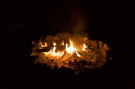 A campfire at night showing logs, flames and burning embers with dark background.